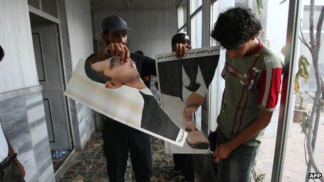 Syrian rebel FSA soldiers tear up a poster of President Bashar al-Assad