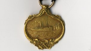 Front of a gold Carpathia medal