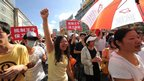 Protesters shout slogans and hold placards outside the local government offices in the coastal city of Qidong