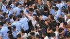 Protesters and police clash outside the local government offices in Qidong