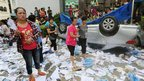 Local residents gather around scattered documents and an overturned car during a protest against plans for a water discharge project in Qidong