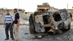 Rebels with destroyed armoured vehicle in Homs. 27 July 2012