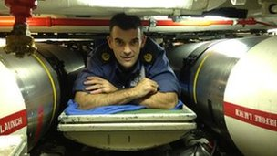 A crew member of HMS Triumph on a bunk bed between cruise missiles