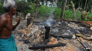 Bodo tribal man stands in debris of his burnt house in Mojati village at Kokrajhar district in Assam