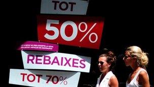Women walk past shop in Barcelona