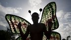Man in a butterfly costume takes part in the parade in Port-au-Prince