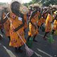 People parading with brooms and dressed in flower-patterned costumes in Port-au-Prince