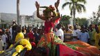 A carnival queen with fruit-studded hat is taken through the parade by car