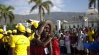 Man with two snakes wrapped around his head in Port-au-Prince