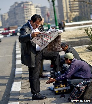 Man reading newspaper in Cairo street