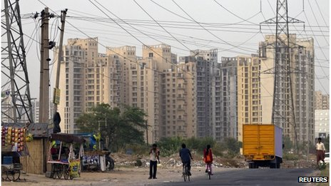 People ride their bicycles under overhead power cables, against the backdrop of multi-story residential apartments at Gurgaon