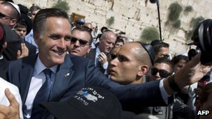 Mitt Romney waves at a camera by the Wailing wall