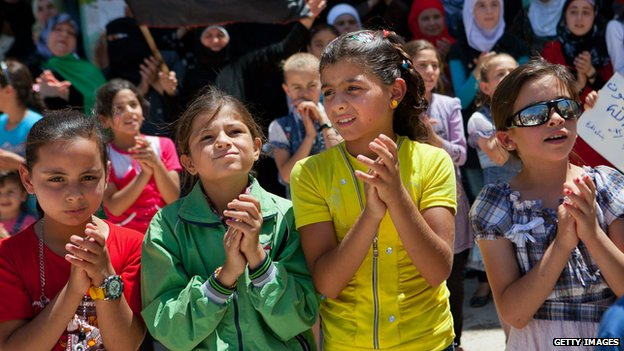 Syrian children clap as they take part in an anti-government demonstration 