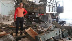 Rebel fighter stands with empty ammunition boxes after capture of government checkpoint at Anadan - 30 July