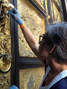 A restorer works on the Gates