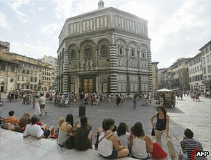 People sit near the Baptistery of San Giovanni in Florence, 26 June 2012