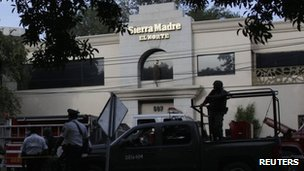 Troops and police stand guard outside El Norte's offices in the municipality of San Pedro Garza, 30 July 2012