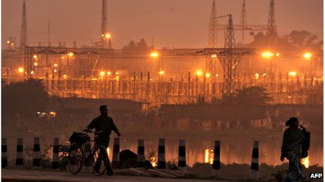 "In this photograph taken on December 9, 2009 pedestrians walk on a roadside past a power sub-station in the outskirts of Kolkata. India""s northern electricity grid which covers an area home to more than 300 million people failed for the second day in a row on July 31, 2012, with the eastern network also down, an official said. A"