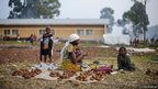 A displaced Congolese woman from Rugari peels potatoes