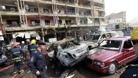 Emergency services personnel at the scene of one of the bombings in Baghdad (31 July 2012)