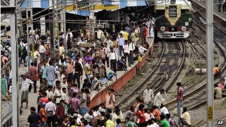 Passengers wait at a railway station in Delhi, India (31 July 2012)