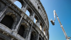 A worker rides on a boom lift as he inspects the Colosseum, 31 July