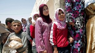 Syrians queuing outside a bakery in the town of Aldana, near Aleppo, on 31 July 2012