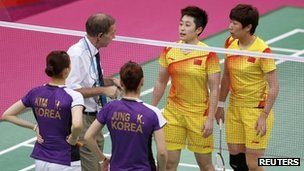Tournament referee Torsten Berg (2nd L) speaks to players from China (in yellow) and South Korea during their women&#039;s doubles group play stage in London on 31 July 2012