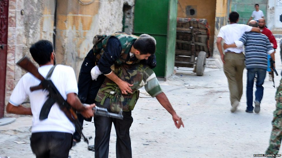 Syrian rebels carry a comrade who was wounded during clashes with ...
