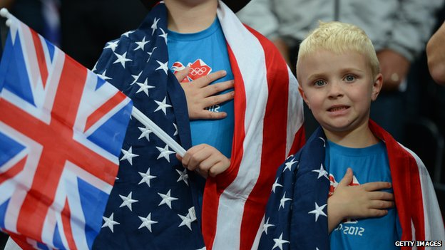Two children draped in American flags, with their hands on their hearts