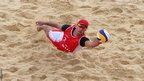 Jefferson Bellaguarda of Switzerland dives for a shot during the men's beach volleyball