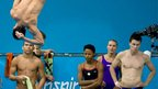 Athletes look on as a diver practices a routine during a training session at the Aquatics Centre
