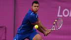 Jo-Wilfried Tsonga of France returns a shot to Milos Raonic of Canada during the second round of men's singles