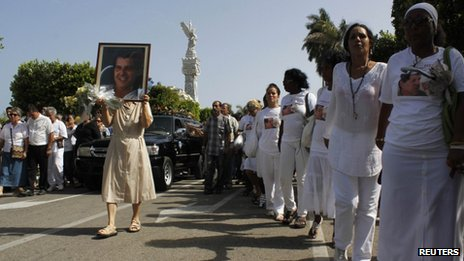 "Members of the ""Ladies in White"" opposition group march beside the funeral procession of Oswaldo Paya on 24 July 2012"