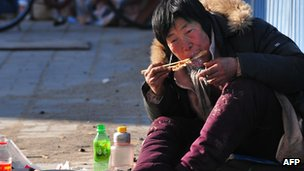Chinese person eating on side of road