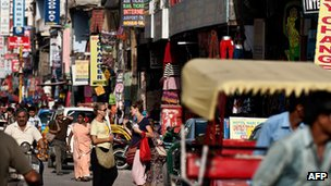 Foreign tourists in a busy street with shops on either side in Paharganj, Delhi