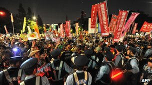 "Protesters hold placards and shout slogans as they take part in a rally in front of Japan""s parliament"