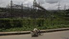 An Indian man pulls his cart past a power station on the outskirts of Gauhati, India