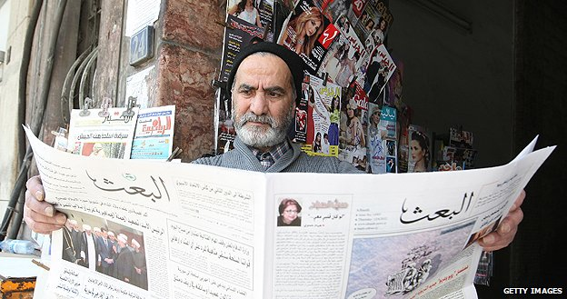 Man reading Al-Baath newspaper