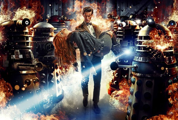 The Doctor carries Amy past a group of Daleks, engulfed in flames