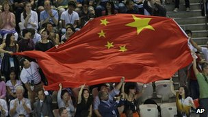 Chinese fans wave their national flag during a winning ceremony at the Aquatics Centre in the London Olympic Park, 29 July 2012