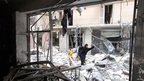 Woman walks through rubble of building destroyed by shelling from pro-Assad forces, central Aleppo (1 August 2012)