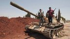Syrian rebel fighters stand on top of a government tank captured two days earlier at a checkpoint in the village of Anadan, about five kilometres (3.8 miles) north-west of Aleppo on 1 August 2012