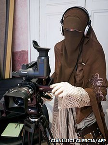 A female camera operator wearing a niqab