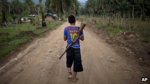 A boy with a rifle slung over his back, patrols an area of La Confianza, Honduras - May 2012