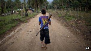 A boy with a rifle slung over his back, patrols an area of La Confianza, Honduras - May 2012