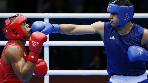 Jose Larduet Gomez (L) of Cuba defends against Ali Mazaheri (R) of Iran