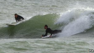 Surfers at the Boscombe reef riding waves