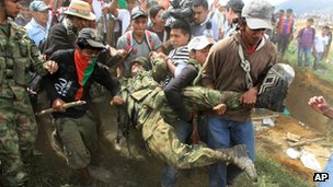 Nasa men drag a soldier from his post in Toribio, Colombia