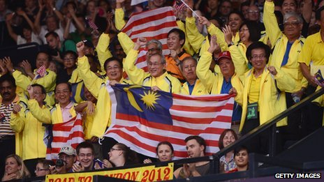Malaysian fans cheer on one of their country's badminton players